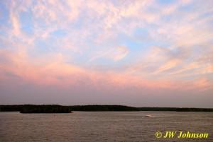 Speedboat Races Across Sunset Sky